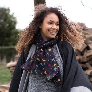 Lovely soft scarf in black with brightly coloured swallow motifs and white stars. Made from recycled plastic bottles