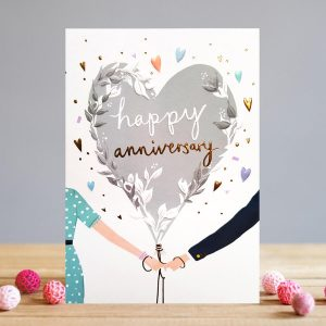 A white rectangular card with a giant silver grey heart shaped balloon being held by a man and woman's hands together. There are hearts and dots printed around the balloon and the words Happy Anniversary are embossed and printed in gold foil effect.