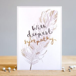 A rectangular card whit and image of a feather which has been embossed and printed with a subtle gold foil effect. The words deepest sympathy are also embossed and printed in black and gold foil.