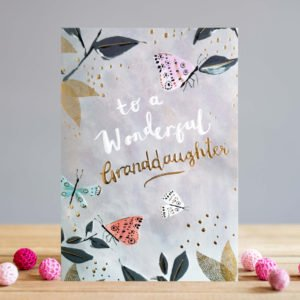 A rectangular card with a pale grey background and images of leaves branches and butterflies on it. The images are highlighted with an embossed gold foil print. The words To a Wonderful Granddaughter are printed in white and gold print.