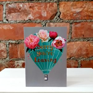 Luxurious leaving card with flowers and a big hot air balloon and in gold foil, the words, Sorry You're Leaving