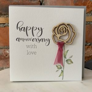 A square white card with the wording Happy Anniversary With Love and a wooden cutout rose which has a hand painted stem and a pink ribbon attached.