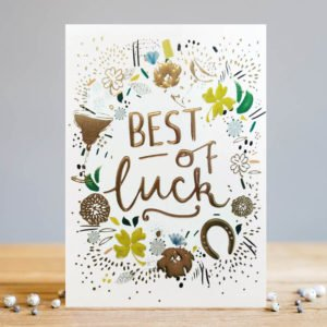 A white rectangular card with the words Best of Luck embossed and printed in a gold foil effect. Around the wording there are painted images of 4 leafed clovers. horse shoes and flowers which als have an embossed gold effect.