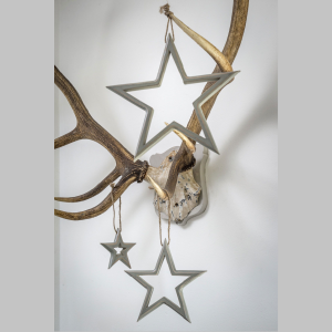 A set of 3 grey cutout stars which are all different sizes. The stars are hanging on a pair of deers antlers.