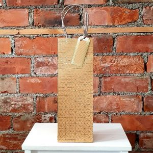 Craft bottle bag with gold geometric patterns and tag on handle