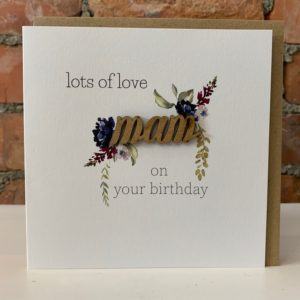 A square white card with the word Mam cut out of wood with hand painted flowers around the wooden lettering. The words Lots of Love on Your birthday are printed above and below Mam.