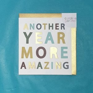 A designer typographic birthday card from Caroline Gardner. A white card with Another year more amazing in colourful letters with some of the letters being punched out.