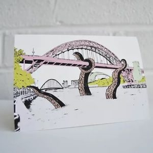 A greetings card with an illustration of a giant sea monster attacking the tyne bridge