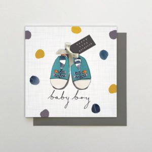 A square white card with colourful spots all over it and a pair of blue shoes in the centre of it. The wording Baby Boy is written underneath the shoes. The card is finished off with a white bow and some sparkly beads.
