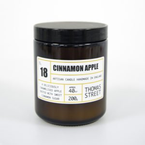 A cinnamon apple candle in a brown apothecary jar with a lid, and with a white label.