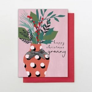 "A luxury Christmas card with the words ""Happy Christmas Granny"". With a Christmas bouquet of flowers in a vase finished with a hand tied black and white stripy bow"