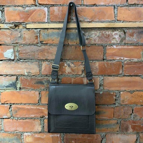 Grey easy to wear medium crossbody bag. Made from synthetic materials in a choice of colours with an adjustable strap. Flap closing with a metal twist fastener. Internal and external pockets.