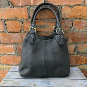 Shoulder bag in grey with buckle details on the handles and zip fastening. Additional pockets on the inside and outside