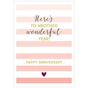 A white card with pink faded stripes running down the card and with the wording Here's to another wonderful year. Happy Anniversary printed on it. There is also a little red heart printed on the card.