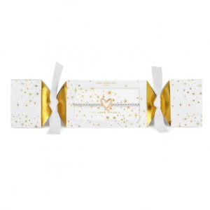 A silver plated bracelet with a gold heart charm which is packaged in a white cracker style box with gold stars printed on it.