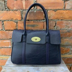 Navy shoulder bag with metal twist fastening and detachable crossbody strap. Internal and reverse zipped pockets