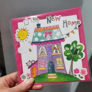 A cheerful new home card. This card is printed on textured board and flittered. It features shaped die-cut edges on three sides with the fold lying at the top of the card.