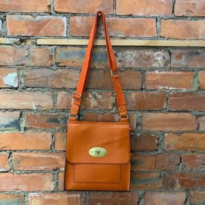 Orange easy to wear medium crossbody bag. Made from synthetic materials in a choice of colours with an adjustable strap. Flap closing with a metal twist fastener. Internal and external pockets.