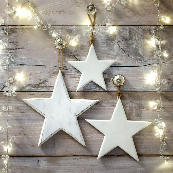 A set of three white wash stars of different sizes, hung with string fastening.