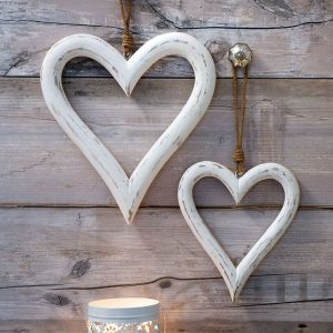 A pair of white wash outline hearts which are of different sizes and are hung with a string fastening.