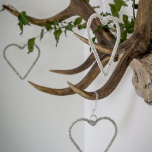 Hanging heart decorations that are made of wire and covered in sparkly seed beads, hung with white ribbons.