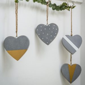 A set of 4 hanging hearts that are grey based, one with white spots, one with a golden tip, one with a white stripe and one with a gold diamond on it.