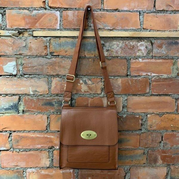Tan easy to wear medium crossbody bag. Made from synthetic materials in a choice of colours with an adjustable strap. Flap closing with a metal twist fastener. Internal and external pockets.