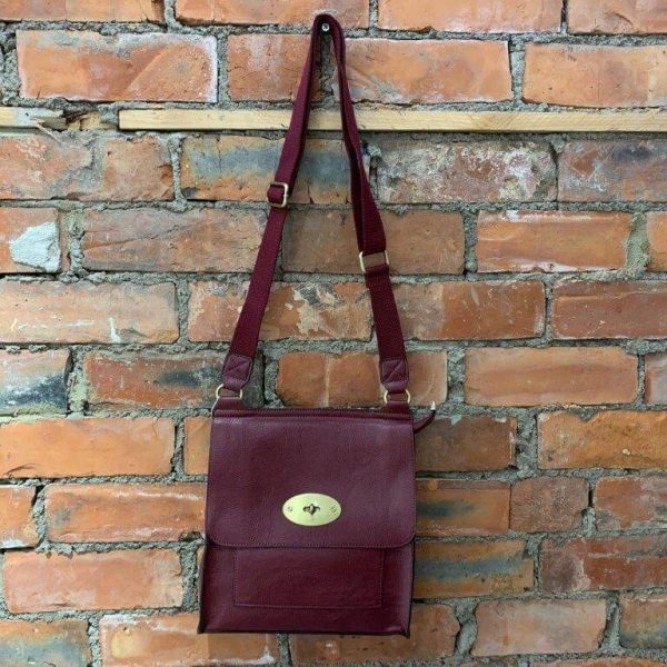 Wine easy to wear medium crossbody bag. Made from synthetic materials in a choice of colours with an adjustable strap. Flap closing with a metal twist fastener. Internal and external pockets.