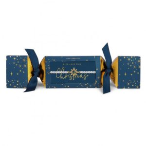 A silver plated bracelet from Joma Jewellery in a dark blue cracker style packaging whit gold stars printed all over it.