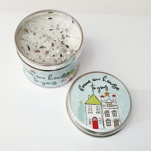 """A christmas scented candle in a tin illustrated with a christmas street scene and """"from our house to yours"""". A lovely gift for a neighbour or friends"""