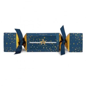A silver plated Joma Jewellery bracelet with a gold star charm in blue cracker style packaging with little gold stars printed on it and blue ribbons at each end.