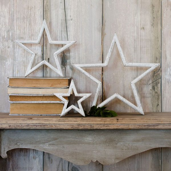 Three white washed wooden stars of different sizes standing on a shelf. From Retreat home.