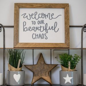A framed print that says Welcome to our beautiful chaos