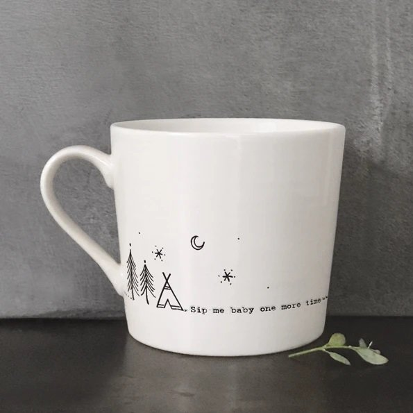 A cream ceramic mug with a black line drawing of a teepee by some trees and the words, Sip me baby one more time. Comes in a gift box