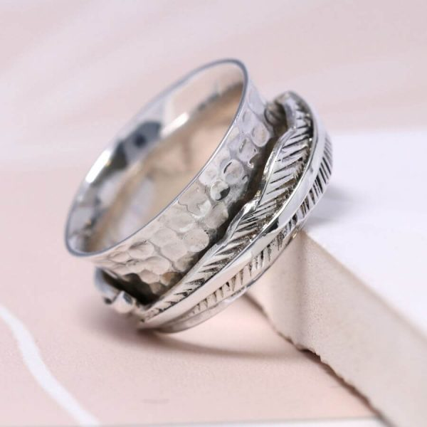 Hand made sterling silver ring with a beaten concave band and two slim connected silver feathers, spinning freely around the band.