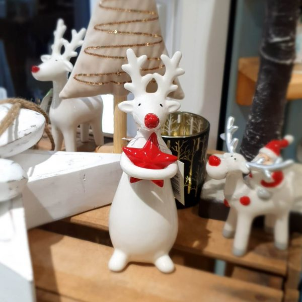 A white ceramic standing reindeer hugging a red star decoration