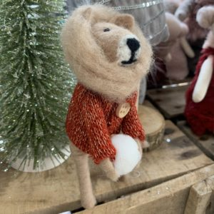 A lion Christmas decoration with a lovely mane, a red jumper and holding a snowball.