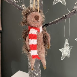 A hedgehog made from felt and wearing a red and white striped scarf