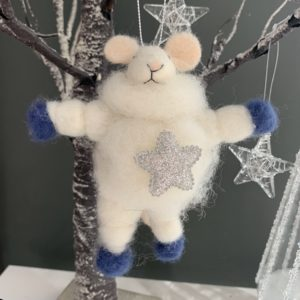 A mouse Christmas decoration, with the mouse wearing a space suit which has a silver star on the front of it.