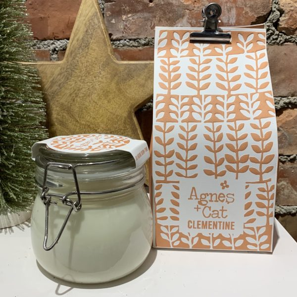 A clementine scented candle from Agnes and Cat. Comes in a kilner jar and is packaged in a colourful bag held closed with a bulldog clip.