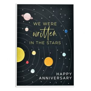 An anniversary card. A black card with tiny silver stars and the planets in metallic foil and embossed in orbit around the sun. The words are We were written in the stars. Happy Anniversary