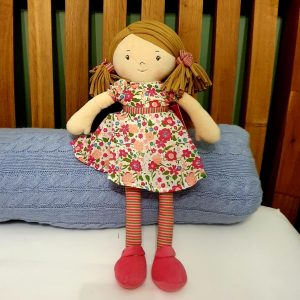 a lovely rag doll with brown hair and a pretty pink floral dress. With stripy tights and matching hair ties she is a perfect gift for a little girl