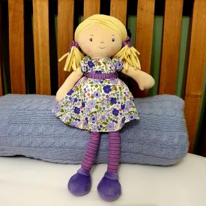 a lovely rag doll with blond hair and a pretty purple floral dress. With stripy tights and matching hair ties she is a perfect gift for a little girl