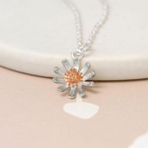 A silver daisy with a rose gold centre on a fine silver chain necklace