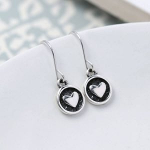 A pair of sterling silver earrings with a silver heart in a disc drop, the disc has been oxidised to black to make the silver heart stand out.