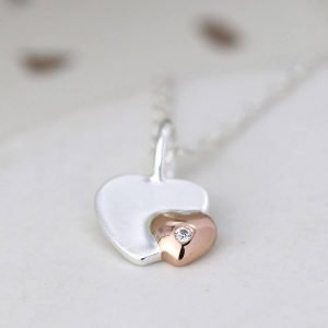 sterling silver necklace with a silver heart and a rose gold plated smaller heart with a crystal detail on a fine silver chain