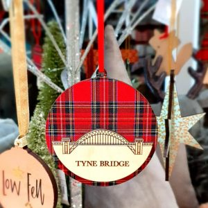 A round hanging decoration with the Tyne Bridge cut out in wood