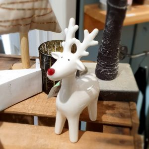 A white ceramic standing reindeer decoration with a cute red nose