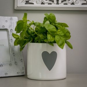 A large white plant pot with a grey heart on the front of it.