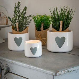 A set of three plant pots with grey hearts on the front of them